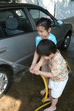 Kids washing car. In a sunny afternoon happily Stock Photos