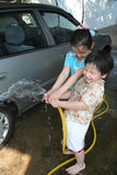 Kids washing car. In a sunny afternoon happily Stock Photo