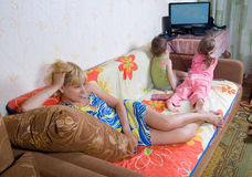 Kids watch cartoons. Mom is resting while the kids watch cartoons royalty free stock images