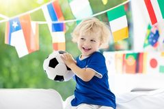 Kids watch football game. Child watching soccer. Child watching football game on tv. Little boy in France tricot watching soccer game during championship. Kid Stock Photos