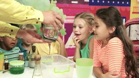 Kids watching animator carry out a science experiment. Experiment with liquid on kids Birthday party. Happy children in entertainment center stock video footage