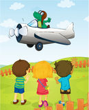 Kids watching crocodile flying plane Stock Images