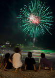 Kids watching the fireworks by the beach on new year eve. Beautiful and colourful fireworks on the seashore on new year eve at Coogee beach in Sydney, Australia Stock Photo