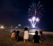 Kids watching the fireworks by the beach on new year eve. Beautiful and colourful fireworks on the seashore on new year eve at Coogee beach in Sydney, Australia Stock Images