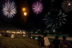 Kids watching the fireworks by the beach on new year eve. Beautiful and colourful fireworks on the seashore on new year eve at Coogee beach in Sydney, Australia Royalty Free Stock Image