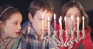 Kids watching hanukka candles burning. Three young Kids watching hanukka candles burning stock video footage