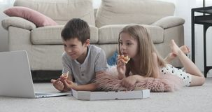 Kids watching movie at home. Little boy and girl eating pizza while watching movie on laptop at home stock video