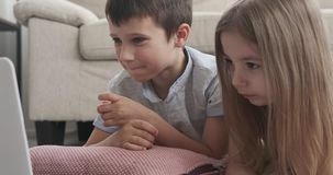 Kids watching movie at home. Little kids enjoying movie on laptop at home stock video
