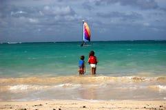 Kids watching sailboat Oahu, Hawaii. Kids watching sailboat on beautiful Lanikai beach, Oahu, Hawaii Stock Photography