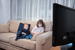 Kids watching television. Two kids sitting on couch watching television Stock Photos