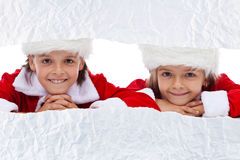 Kids watching the unwrapping christmas present Royalty Free Stock Photos
