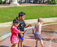 Kids in Water Park. Picture of Caucasian and Asian kids playing on a splash pad on the River Walk in Montgomery, Alabama during the Second Saturdays event stock photo