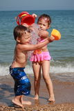 Kids watering on the beach. Little girl pooring a bucket of water on her little brother Stock Photography