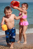 Kids watering on the beach 2. Little girl pooring a bucket of water on her little brother Royalty Free Stock Image