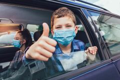 Kids wearing anti virus masks and using digital tablets in the car. Kids are travelling in car