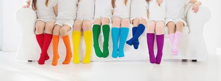 Kids with colorful socks. Children footwear. Kids wearing colorful rainbow socks. Children footwear collection. Variety of knitted knee high socks and tights Royalty Free Stock Photography