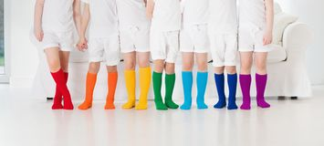 Kids with colorful socks. Children footwear. Kids wearing colorful rainbow socks. Children footwear collection. Variety of knitted knee high socks and tights Stock Image