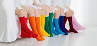 Kids with colorful socks. Children footwear. Kids wearing colorful rainbow socks. Children footwear collection. Variety of knitted knee high socks and tights Stock Images