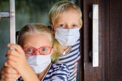 Kids wearing face masks peeking out the door