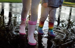 Kids wearing striped wellingtons in the puddle Stock Image
