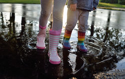Kids wearing wellingtons in the puddle. Playing kids wearing striped wellingtons in the puddle with sun in the back Royalty Free Stock Image