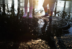 Kids wearing wellingtons in the puddle Royalty Free Stock Images