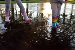Kids wearing wellingtons in the puddle. Playing kids wearing striped wellingtons in the puddle with sunny background Royalty Free Stock Photography
