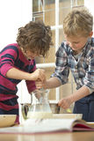 Kids whisking batter. Two kids whisking batter in a bowl during a baking workshop at home at a birthday party royalty free stock photos