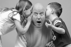 Kids Whispering to Dad Royalty Free Stock Images