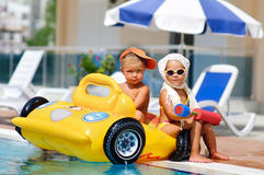 Kids whit infatable toys in pool. Cute toddler boy and girl sit in infatable car in pool outdoor Stock Photography