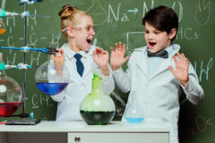 Kids in white coats with chalkboard behind in laboratory, scientists kids team concept Stock Photos