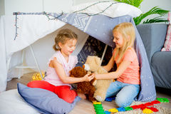 Kids in a wigwam. Two girls playing together in a wigwam in a living room stock photo