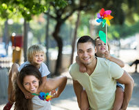 Kids with windmills on parent's arms Stock Image