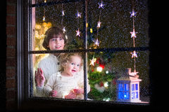 Kids at window on Christmas eve Royalty Free Stock Photography