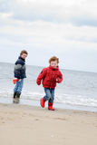 Kids at winter beach. Two boys (9 and 4) in winter clothing at the beach, running away from the waves and having fun. Photo taken on an early spring day stock photos