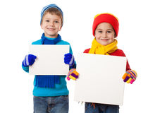Kids in winter clothes with empty blanks Royalty Free Stock Photos