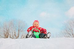 Kids winter fun- little girl enjoy sliding in snow. Nature stock image