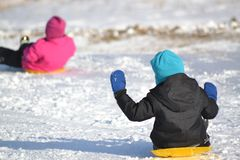 Kids winter fun sledding. Boy and girl sledding down hill on sunny day on field covered with snow Stock Photo