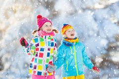 Kids winter snow ball fight. Children play in snow. Kids playing in snow. Children play outdoors on snowy winter day. Boy and girl catching snowflakes in Royalty Free Stock Photography
