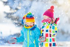 Kids winter snow ball fight. Children play in snow. Kids playing in snow. Children play outdoors on snowy winter day. Boy and girl catching snowflakes in Stock Photo