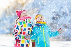 Kids winter snow ball fight. Children play in snow. Kids playing in snow. Children play outdoors on snowy winter day. Boy and girl catching snowflakes in Royalty Free Stock Image