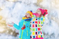 Kids winter snow ball fight. Children play in snow Stock Photo