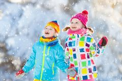 Kids winter snow ball fight. Children play in snow. Kids playing in snow. Children play outdoors on snowy winter day. Boy and girl catching snowflakes in Stock Image