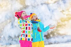 Kids winter snow ball fight. Children play in snow. Kids playing in snow. Children play outdoors on snowy winter day. Boy and girl catching snowflakes in Stock Photos