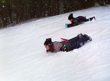 Kids Winter Sport Ontario Canada. Brother and sister enjoy a day snow sledding royalty free stock images