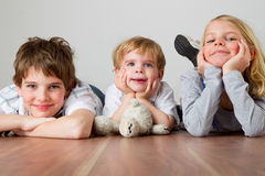 Kids on the wodden floor. Two boys and one girl are lying on the floor royalty free stock photos