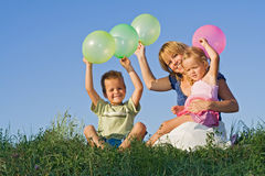 Kids and woman with balloons outdoors Stock Photo