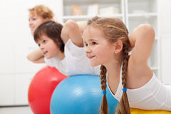 Kids and woman doing exercises with balls Royalty Free Stock Photography