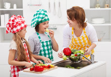 Kids and woman in the kitchen Royalty Free Stock Photos