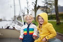 Kids on wooden boat in Holland. Family on boat in Holland, sailing in Amsterdam channels. Dutch family with kids on traditional residential yacht. Wooden ship in stock photo